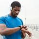 Athlete examining his pulse on fitness bracelet - PhotoDune Item for Sale