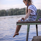 Cute little girl sitting and dreaming on the fisherman wooden pier - PhotoDune Item for Sale