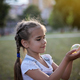 Girl with two braids holding in her palms big soap bubble - PhotoDune Item for Sale