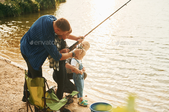 Learning to fishing. Father and mother with son and daughter together outdoors at summertime - Stock Photo - Images