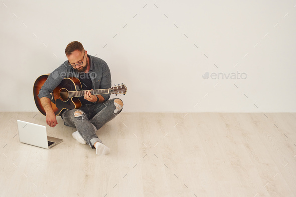With laptop. Man in casual clothes and with acoustic guitar is indoors - Stock Photo - Images