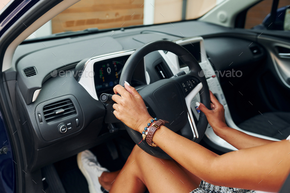 Holding steering wheel. Woman in casual clothes is sitting in her automobile at daytime - Stock Photo - Images
