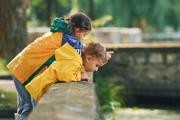 Looking at the river. Kids having fun outdoors in the park after the rain - Stock Photo - Images