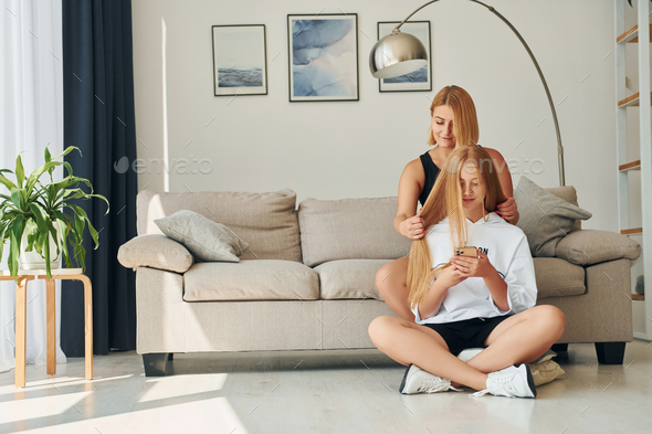 With phone in hands on the floor. Female teenager with her mother is at home at daytime - Stock Photo - Images