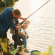 Learning to fishing. Father and mother with son and daughter together outdoors at summertime - PhotoDune Item for Sale