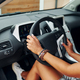 Holding steering wheel. Woman in casual clothes is sitting in her automobile at daytime - PhotoDune Item for Sale