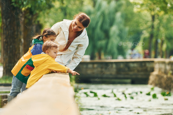 Mother with her little son and daughter have a walk outdoors in the park after the rain - Stock Photo - Images