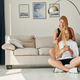 With phone in hands on the floor. Female teenager with her mother is at home at daytime - PhotoDune Item for Sale