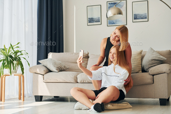 Making selfie. Female teenager with her mother is at home at daytime - Stock Photo - Images