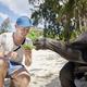 Happy traveler with giant tortoise on beach - PhotoDune Item for Sale
