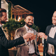 Three handsome men in suits toasting with whiskey and smiling while spending time on party - PhotoDune Item for Sale