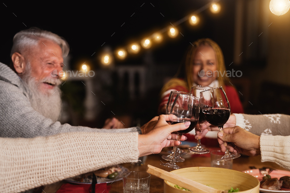 Happy multiracial seniors toasting with red wine glasses and celebrating holidays on house patio - Stock Photo - Images