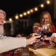 Happy multiracial seniors toasting with red wine glasses and celebrating holidays on house patio - PhotoDune Item for Sale