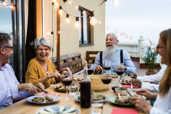 Happy senior friends having fun dining together on house patio - Stock Photo - Images