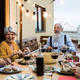 Happy senior friends having fun dining together on house patio - PhotoDune Item for Sale