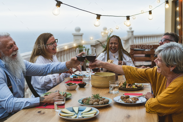 Multiracial senior friends having fun dining together and toasting with red wine on house patio - Stock Photo - Images