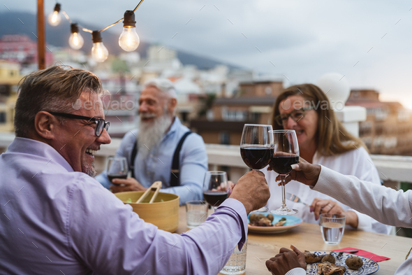 Happy multiracial seniors toasting with red wine glasses together on house patio dinner - Stock Photo - Images