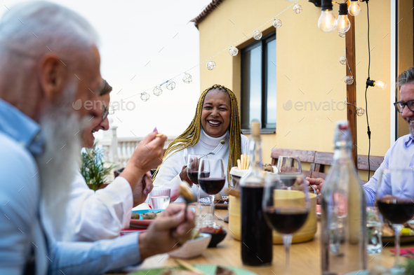 Happy multiracial senior friends having fun dining together on house patio - Stock Photo - Images
