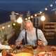 Happy multiracial senior friends having fun dining together on house patio - PhotoDune Item for Sale