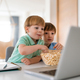 Cute children playing, watching movie on laptop at home. Digital addiction concept - PhotoDune Item for Sale
