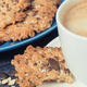 Cup of coffee with milk and fresh baked oatmeal cookies on blue plate. Delicious crunchy dessert - PhotoDune Item for Sale