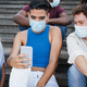 Young diverse people having fun using mobile phones while wearing safety masks outdoor - PhotoDune Item for Sale