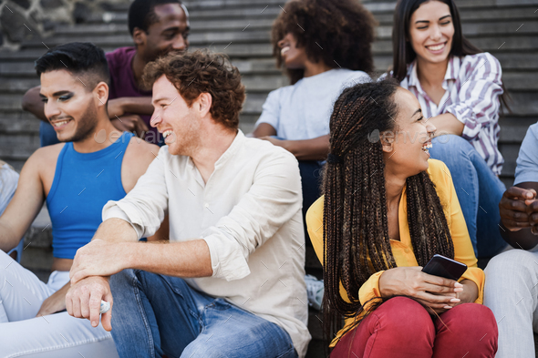 Young diverse people having fun outdoor laughing together - Focus on right african girl face - Stock Photo - Images