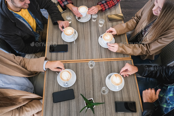 Young friends drinking cappuccino inside vintage bar - Main focus on bottom hands holding cups - Stock Photo - Images