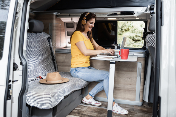 Senior woman having fun using laptop and wearing headphones inside camper mini van - Focus on - Stock Photo - Images