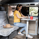 Senior woman having fun using laptop and wearing headphones inside camper mini van - Focus on - PhotoDune Item for Sale
