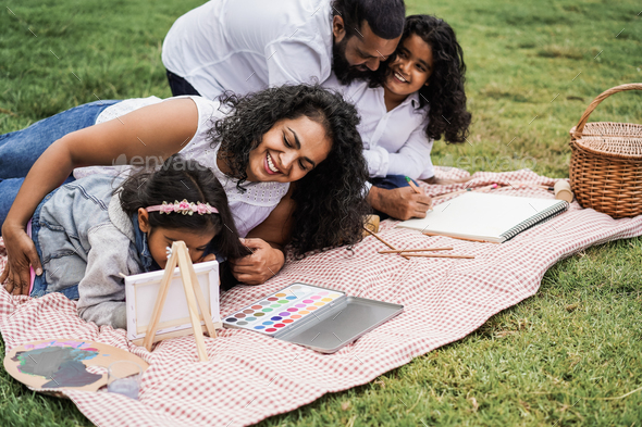 Happy indian family having fun painting with children outdoor at city park - Focus on mother face - Stock Photo - Images