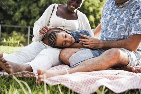 Multiracial family having tender moment doing picnic outdoor at city park - Focus on boy face - Stock Photo - Images