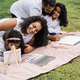 Happy indian family having fun painting with children outdoor at city park - Focus on mother face - PhotoDune Item for Sale
