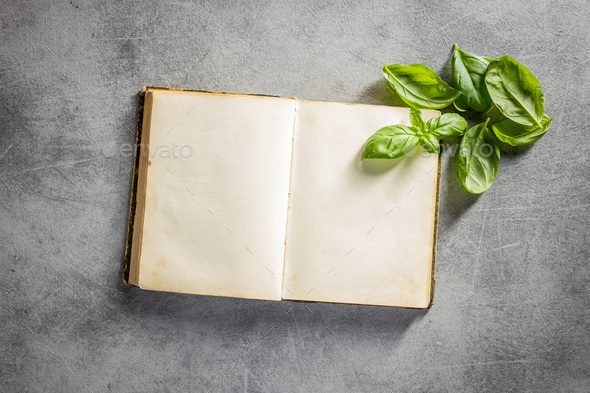Blank recipe book. Cookbook and green basil leaves. - Stock Photo - Images