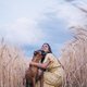 Happy young man hugging his dog while enjoying the day together outdoors in a wheat field. - PhotoDune Item for Sale