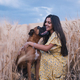 Portrait of a cheerful young woman having fun and enjoying nature with her dog in a wheat field. - PhotoDune Item for Sale