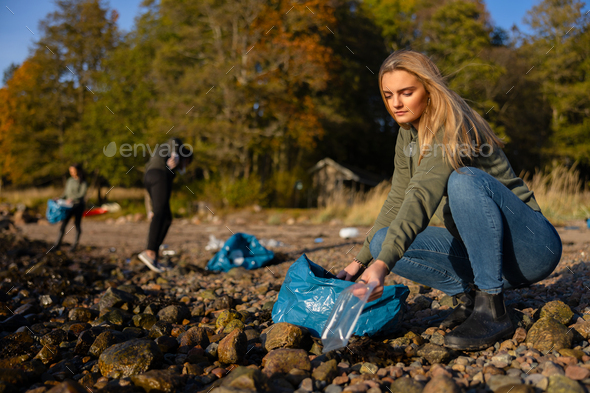 Serious young woman in environment conservation team picking up plastic at beach - Stock Photo - Images