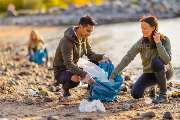 Team of dedicated and smiling volunteers collecting plastic garbage at beach - Stock Photo - Images