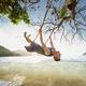 Man on swing enjoying beautiful sunset on beach - PhotoDune Item for Sale
