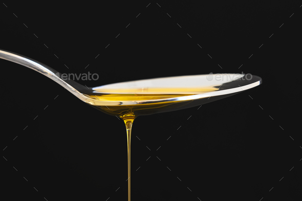 Olive oil drop on a spoon over black background. Cooking - Stock Photo - Images
