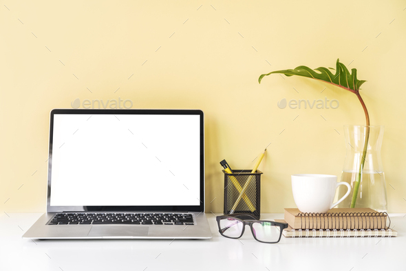 Modern and stylish workspace mock up with blank laptop and desk office supplies - Stock Photo - Images