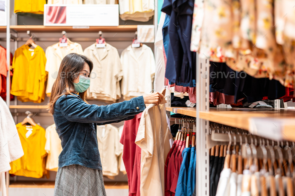 Young Asian woman wearing surgical mask shopping in clothes stores at the mall - Stock Photo - Images