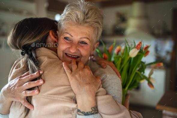 Happy senior mother hugging adult daughter indoors at home, mothers day or birthday celebration - Stock Photo - Images