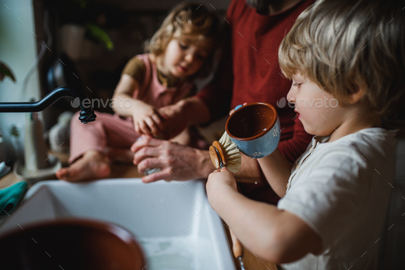 Unrecognizable father with two small children washing dishes indoors at home, daily chores concept - Stock Photo - Images
