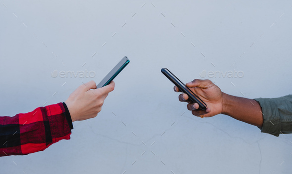 Close up of young mixed couple hands using smartphones on white background - Stock Photo - Images