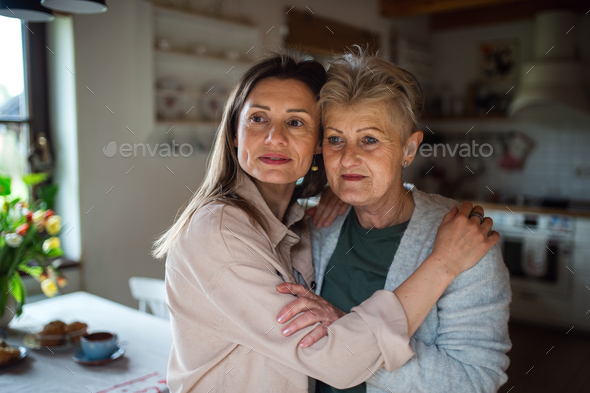 Portrait of senior mother hugging with adult daughter indoors at home, looking aside - Stock Photo - Images