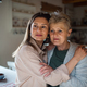 Portrait of senior mother hugging with adult daughter indoors at home, looking aside - PhotoDune Item for Sale