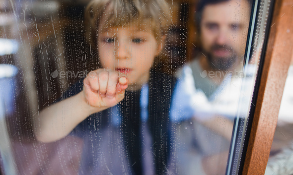 Sad boy with unrecognizable father looking through dirty window, housework concept - Stock Photo - Images