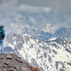Hiker woman standing up achieving the top. View at the snowy mountains. - PhotoDune Item for Sale