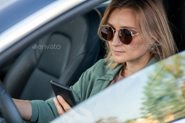 Young contemporary woman driving car and texting - Stock Photo - Images